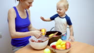Mom and little boy cook food together in kitchen
