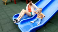 Mom and son have fun on the slide
