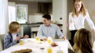 Mutter mit einem Krug Milch zum Frühstück Tisch