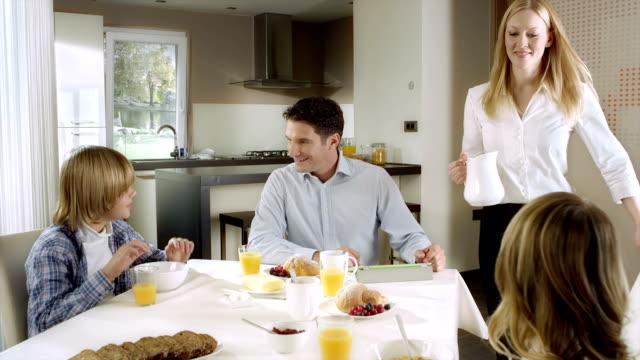 Madre portando una Brocca di latte al tavolo per la prima colazione