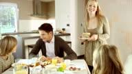 Madre portando Pancake alla sua famiglia seduta al tavolo