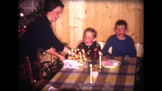 1963 mom brings in birthday cake, boy blows out candles