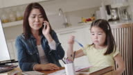 Mom entrepreneur talking on phone and looking after daughter