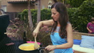 Mom grills brunch in the backyard - scrambled eggs - cam moves in