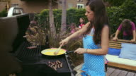Mom grills brunch in the backyard - scrambled eggs - cam moves out