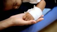 Mom holding sick baby's hand, HD.