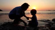 Mamma Baciare Suo figlio sulla spiaggia