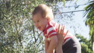 Mom throwing one year old baby in the air while outside in the garden