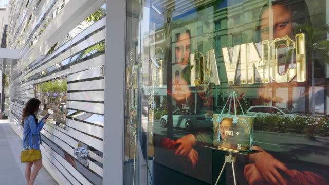 Mona Lisa painting by Leonardo Da Vinci on electronic digital advertising fashion window display at the luxurious boutique store on Rodeo Drive in Beverly Hills, Los Angeles, California, 4K
