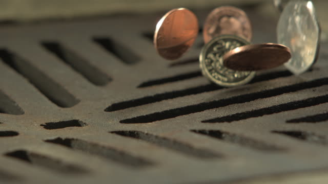 Money Down the Drain - High speed English coins falling on and in to road drain, low angle, cu