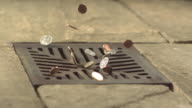 Money Down the Drain - High speed various English coins falling on and in to road drain, wide