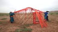 Mongolians in traditional Deel building a yurt in Gobi desert, Mongolia