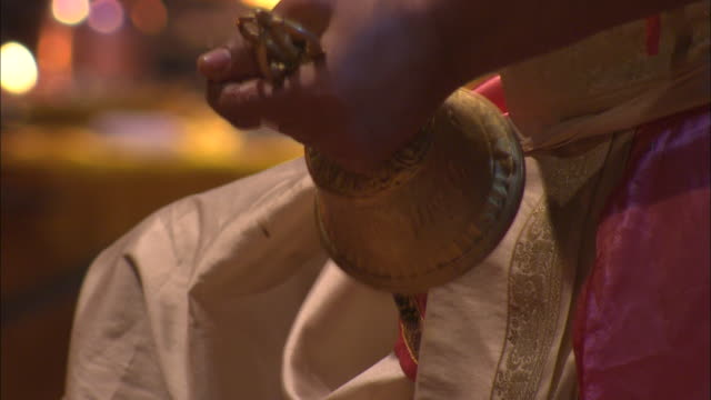 A monk rings bells during a puja ritual for Diwali.