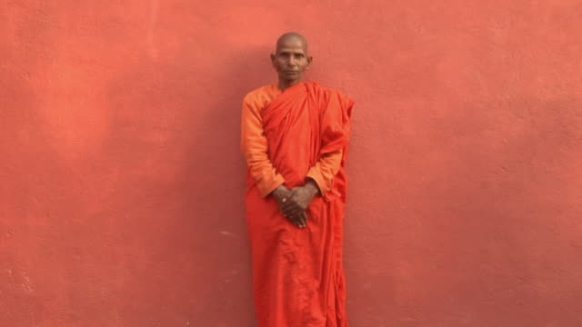 SLO MO MS Monk standing in front of wall as other monks walk past / Bodh Gaya, Bihar, India