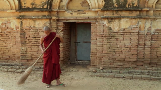 ZO WS HA Monk sweeping dirt road in front of old building / Burma