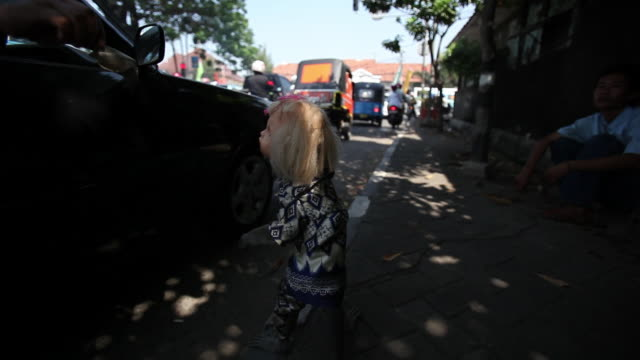 Monkey dressed as doll begs money from car on streets of Jakarta.
