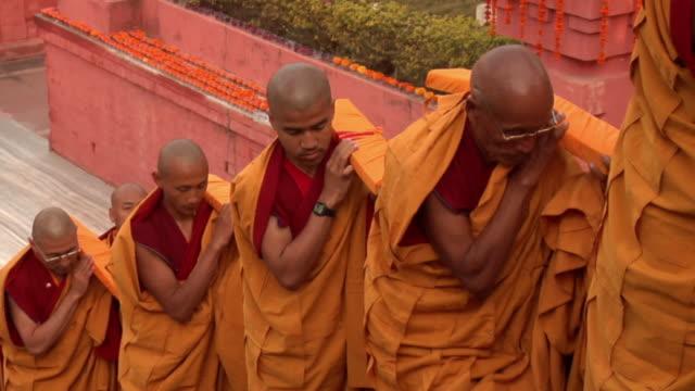 SLO MO HA MS Monks climbing up stairs at Mahabodhi Temple / Bodh Gaya, Bihar, India