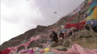 Monks throw confetti into the air from among a hillside of Tibetan prayer flags.