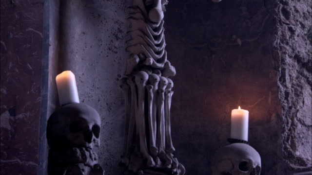A monstrance made of human bones hangs from a wall.\n Available in HD.