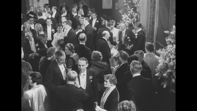 Montage crowd in lobby of Royal Opera House for gala performance of 'Gloriana' during festivities surrounding Elizabeth II's coronation / British...