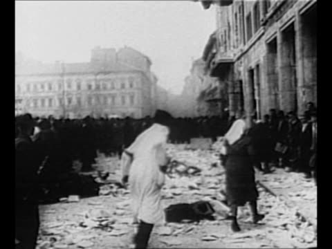 Montage documents from Soviet propaganda center lie on ground outside the building as more documents are thrown from above onto the pile / montage...