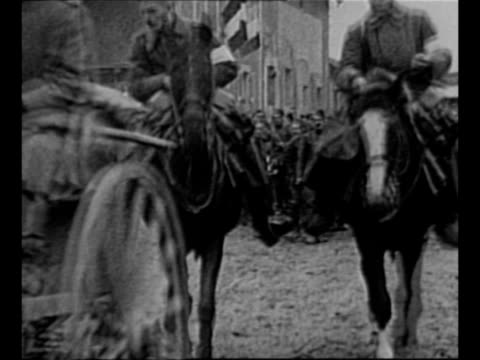 Montage German officers and soldiers move in street / freed World War I French and Italian POWs walk in line through Cologne many waving caps /...