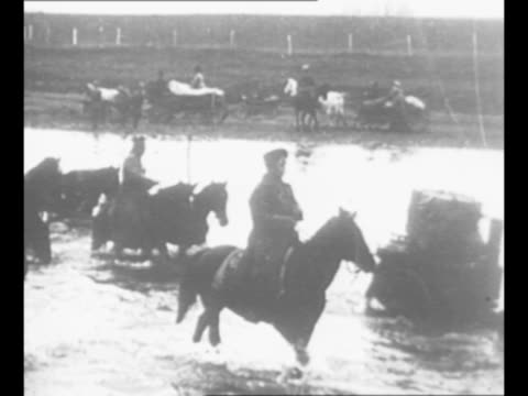 Montage Imperial Russian Army soldiers ride horses pull carts through deep water during World War I / car approaches stops Czar Nicholas II decars...