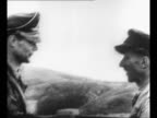 Montage Italian officer with Benito Mussolini's entourage approaches German officer and they shake hands / Mussolini wearing dark clothing and a...