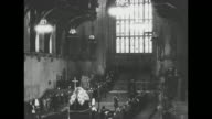 Montage lines of mourners enter Westminster Hall in London file past coffin of Queen Mary as it lies in state on catafalque / MS coffin / Life Guards...