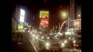 / montage night traffic passing through Times Square crowded sidewalk with sign for Broadway show 'Me and my Girl sign for Howard Johnson's visible...