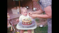 Montage of a young boy being presented his birthday cake on his birthday.