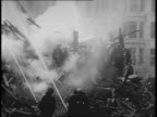 Montage of burning buildings and firefighters at night in Glasgow Scotland after German air raids / various angles of burning building / group of...