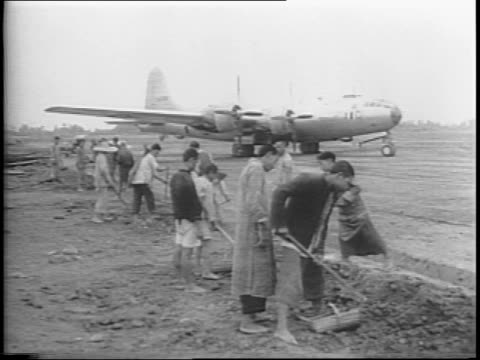 Montage of dozens of B29s on base Chinese laborers stockpile of gas drums detail of plane preparations for mission soldiers lined up send off from...