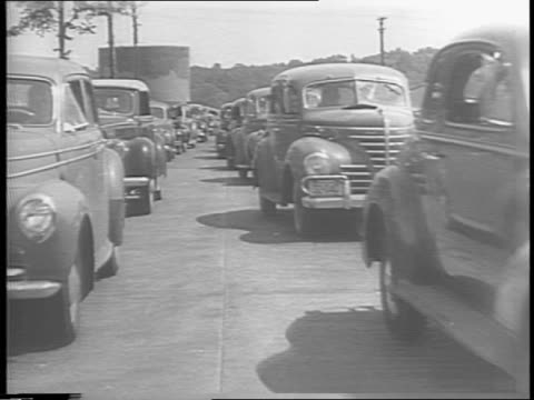Montage of factory workers making rubber tires on an assembly line / lines of cars moving down a road / montage of cars with instructions for...
