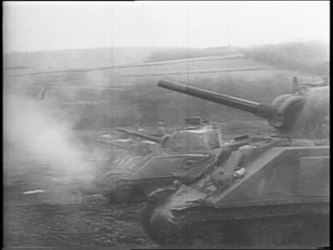 Montage of General George Patton standing on platform addressing group of officers saluting from jeep tanks in snowy field tank cannons firing in row...