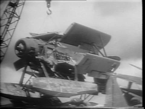 Montage of Japanese planes in flight / Marines dissembling a Japanese war plane / montage of stripped plane being placed on scrap pile by crane /...