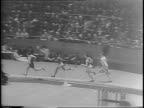 Montage of packed Madison Square Garden arena 60 yard dash race beginning with participants taking off from starting point and sprinting down the...