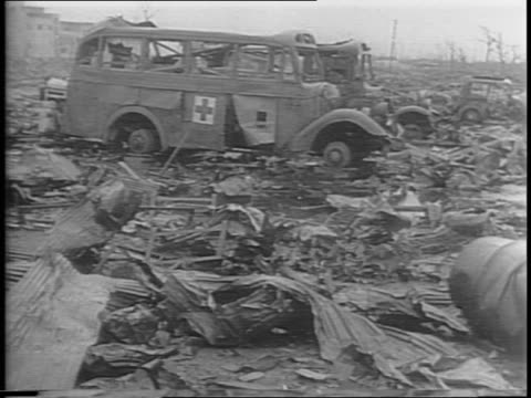 Montage of ruins and rubble in Hiroshima twisted metal and broken buildings a street car and an ambulance stand abandoned and burnt out civilians...
