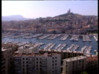Montage of views around Marseilles port including apartment buildings yachts in harbor and traffic on outskirts