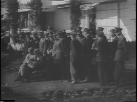 Montage of views of Franklin D Roosevelt and Winston Churchill posed outside Anfa Hotel with members of war council / Roosevelt and Churchill seen...
