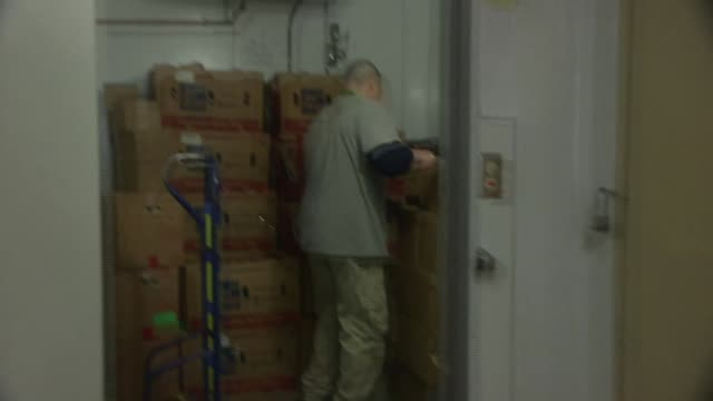 Montage people with shopping carts at food bank volunteer moves dolly filled with boxes of food from freezer