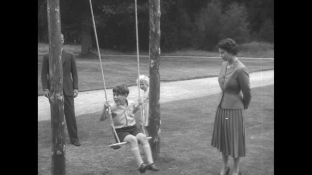 Montage Philip Duke of Edinburgh pushes Prince Charles on a swing on grounds of Balmoral Castle as Queen Elizabeth II and Princess Anne look on...