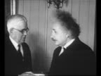 Montage physicist Albert Einstein receives the Benjamin Franklin Medal in 1935 stands with men medal in a hand ceremony in Philadelphia PA / man...