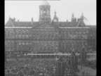 Montage Queen Wilhelmina Princess Juliana Prince Bernhard enter balcony of Royal Palace in Amsterdam / WS Royal Palace with crowds in front / Queen...