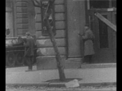 Montage Soviet tanks ride in Budapest gun turrets swivel tanks fire / two people run dive for cover / group of citizens with a corpse tank stands...