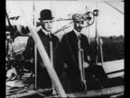 Montage still Orville and Wilbur Wright seated in one of their Wright Flyer airplanes / Wright Brothers fly their airplane / from Greatest Headlines...