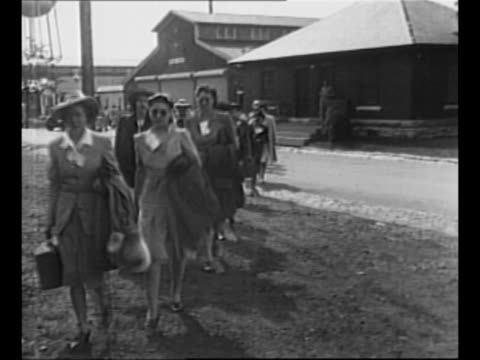 Montage two lines of women walk with US Army officer along street and on grounds of Fort Des Moines Provisional Army Officer Training School women...