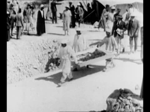 Montage workers at archaeological dig in Egypt carry pallet containing relics from the tomb of King Tutankhamen armed guards follow / workers wade...