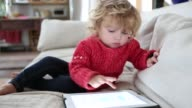 14 month old toddler boy playing with a digital tablet computer