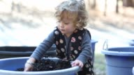14 month old toddler boy playing with bins of soil